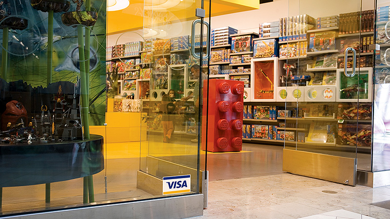 A toy store retailer with the Visa logo displayed at the entrance.